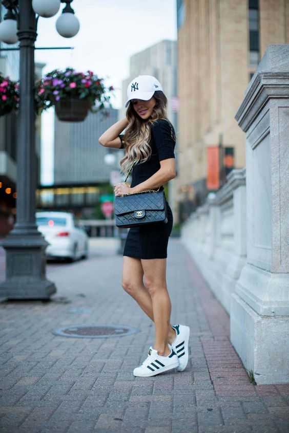 a black t shirt mini dress, white sneakers, a white baseball cap and a black bag for every day