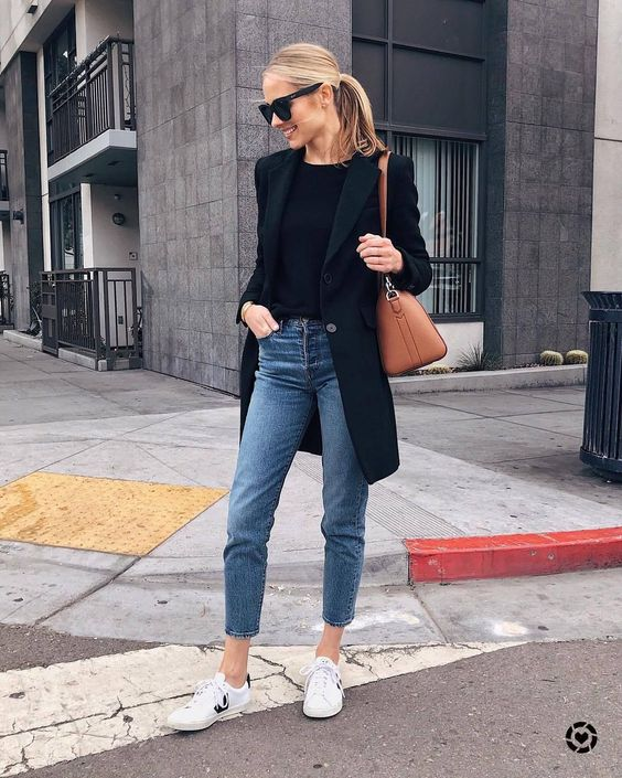 a black top, a black oversized blazer, blue moms, white sneakers and a tan bag