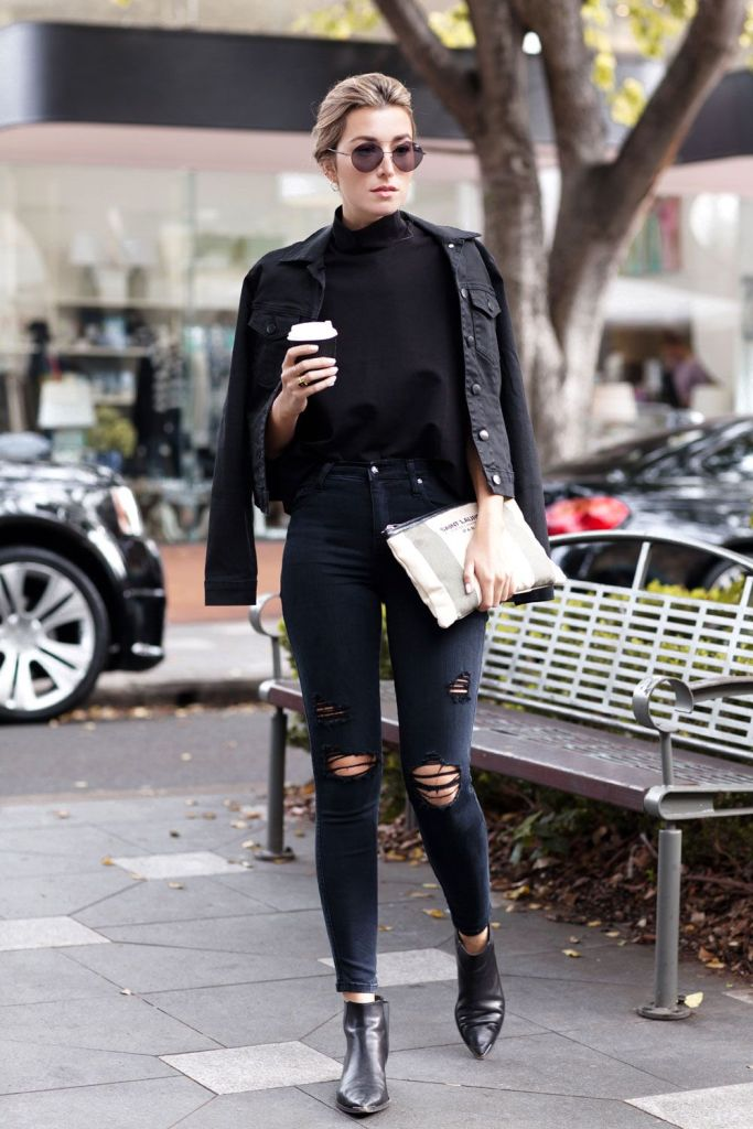 a black top, black ripped jeans, black booties and a black denim jacket plus a clutch