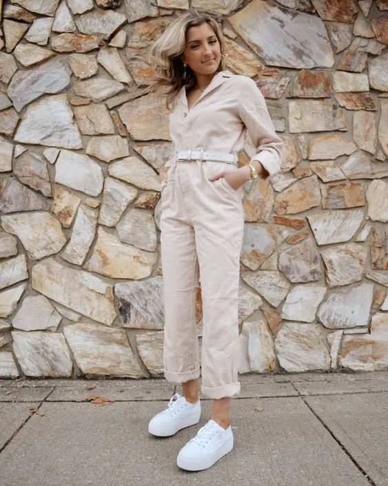 a blush cargo jumpsuit with a white belt, white platform sneakers and elegant accessories to rock