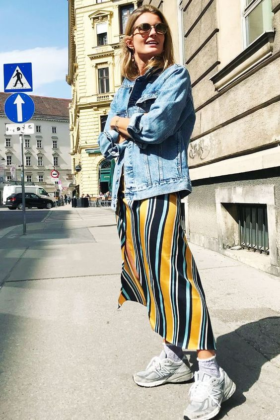 a bright striped slip dress, an oversized blue denim jacket, grey dad trainers and white socks