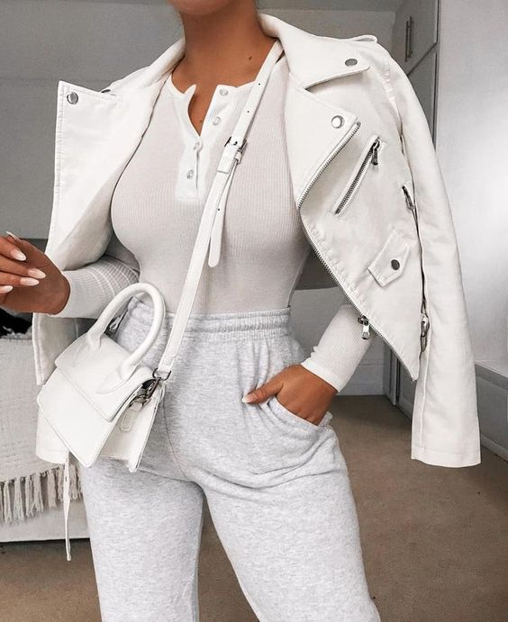 a casual look with a white button up top, grey joggers, a white leather jacket and a white mini bag