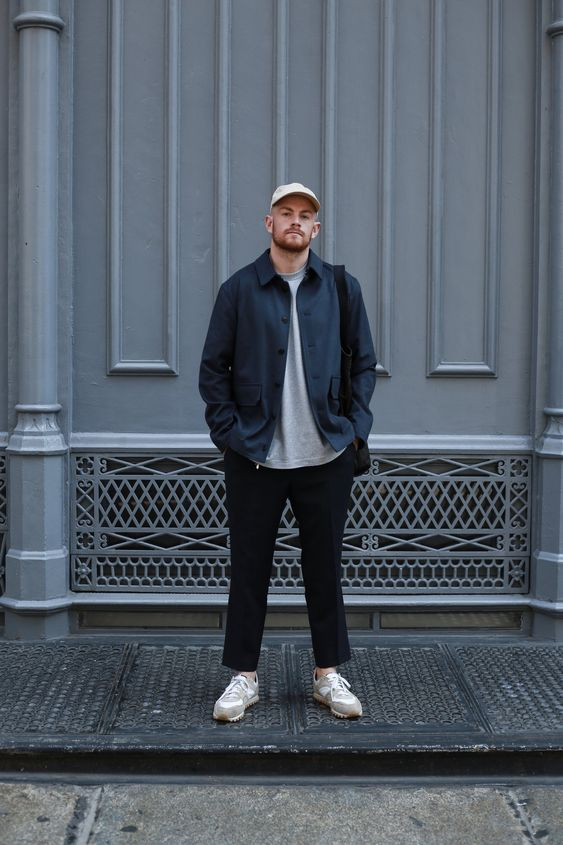 a casual outfit with a grey t shirt, a navy shirt jacket, grey trainers, black trousers and a white baseball hat