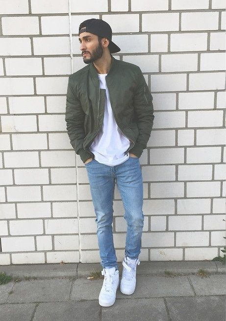 a casual outfit with a white tee and trainers, blue jeans and a dark green bomber jacket plus a black baseball hat