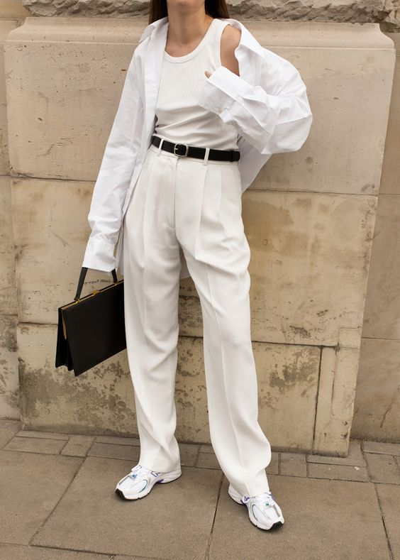 a casual work look with creamy trousers and a top, a white shirt, white trainers and a black bag