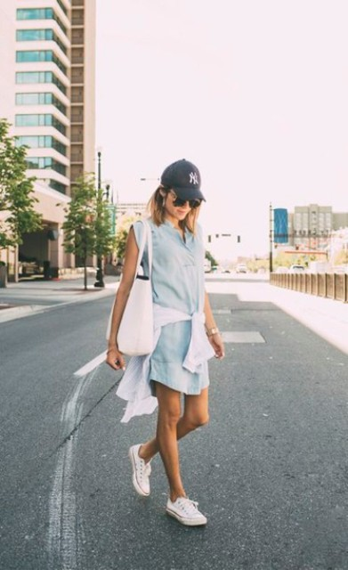 a chambray mini dress, a white jumper, white sneakers, a white tote and a black baseball hat