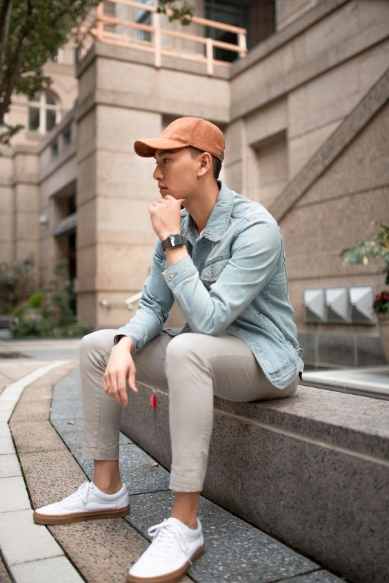 a chambray shirt, grey trousers, white sneakers and a coral baseball cap for spring