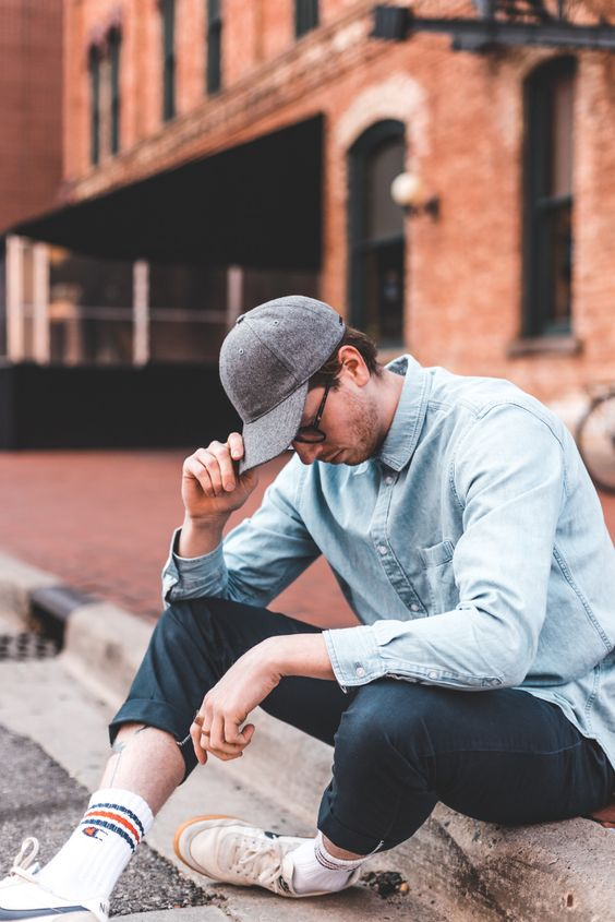 a chambray shirt, teal pants, white sneakers and socks plus a grey baseball cap for spring