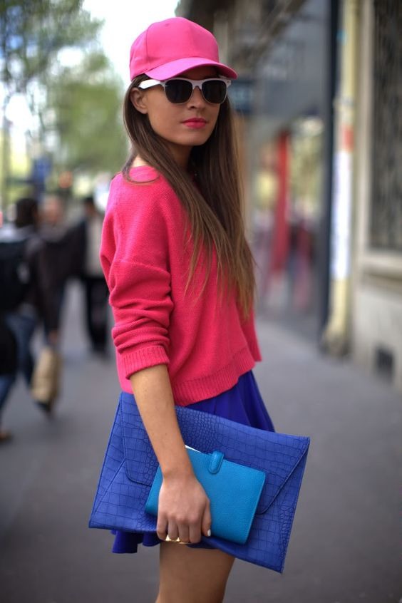 a colorful outfit with a bold blue A-line mini, a pink jumper, a pink baseball hat and a blue clutch