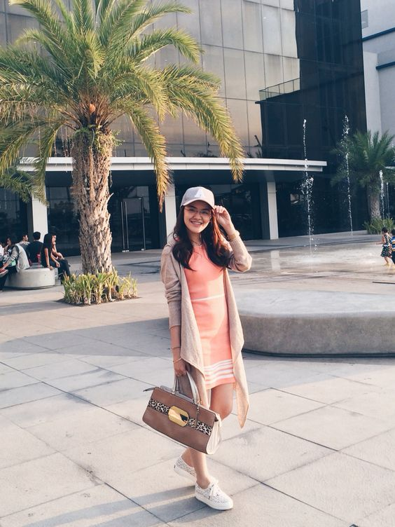 a coral over the knee dress, a grey cardigan, white sneakers, a grey baseball hat and a tan bag