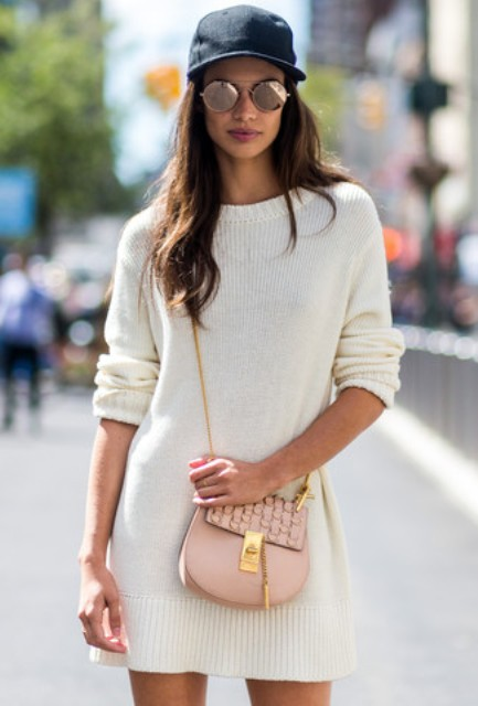 a creamy mini sweater dress, a pink crossbody bag, a navy baseball hat and sunglasses