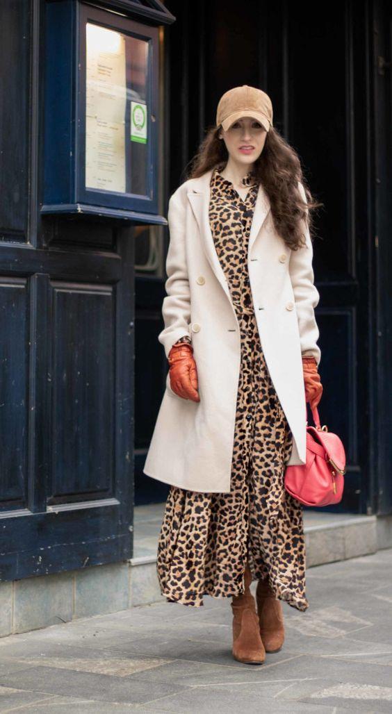 a creative look with a leopard print maxi dress, camel boots, a creamy midi coat, a tan baseball cap and a red bag