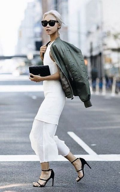 a creative white midi dress with a tiered skirt, a green bomber jacket, black strappy heels and a clutch