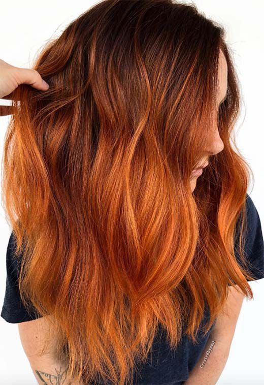 a dark to ginger balayage on long and wavy hair is a bold idea for those who want a trendy look