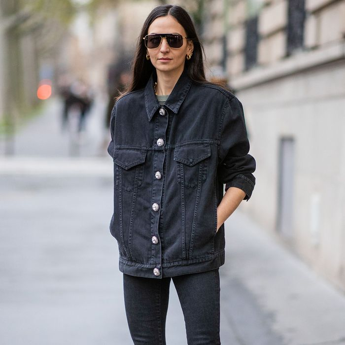 a double denim outfit with an oversized black jacket, skinnies and statement accessories