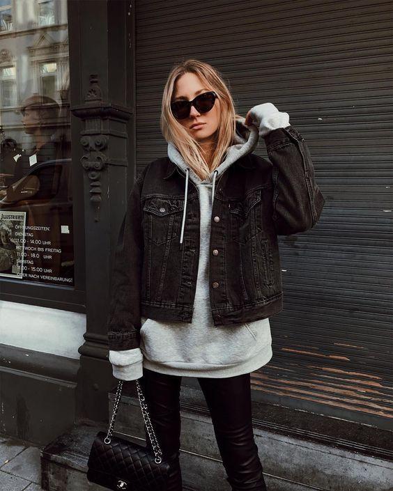 a grey hoodie, a black denim jacket, black leather pants, a black bag for a comfy look