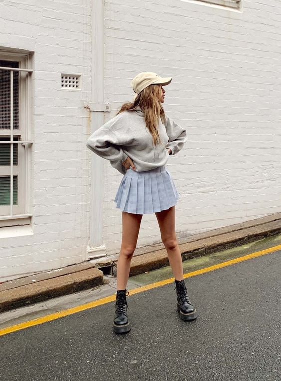 a grey oversized hoodie, a blue pleated mini skirt, a tan baseball cap and black combat boots