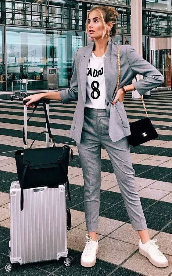 a grey pantsuit, a white printed t shirt, white platform sneakers and a black velvet crossbody bag