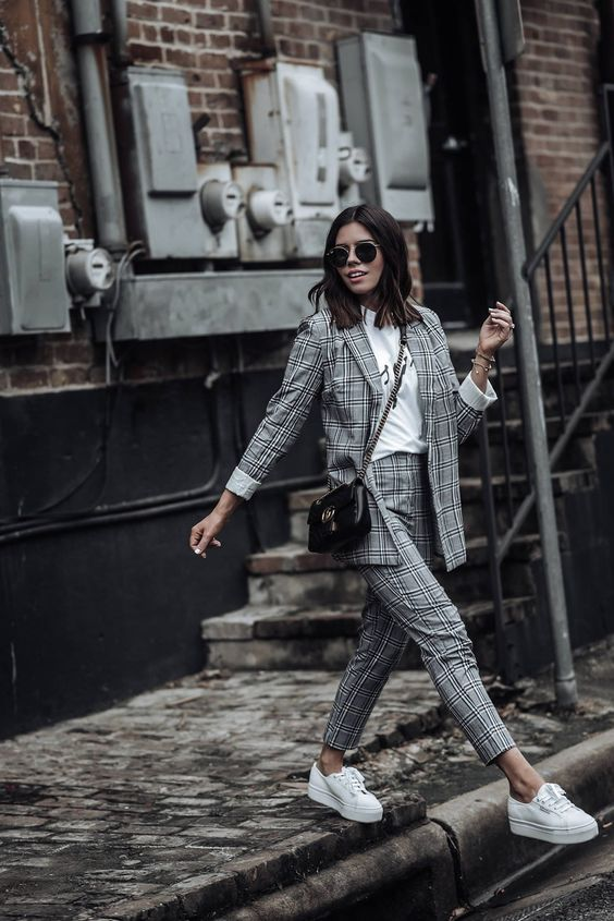 a grey plaid pantsuit, a white long sleeve top, white platform sneakers and a black crossbody bag