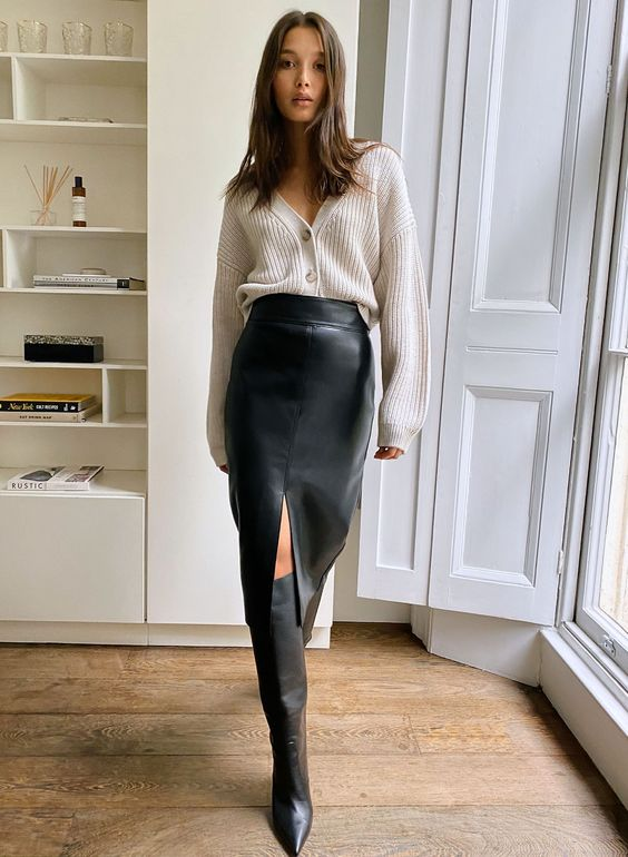 a high-rise black pencil skirt with a front slit, a neutral cardigan as a shirt and black wide boots