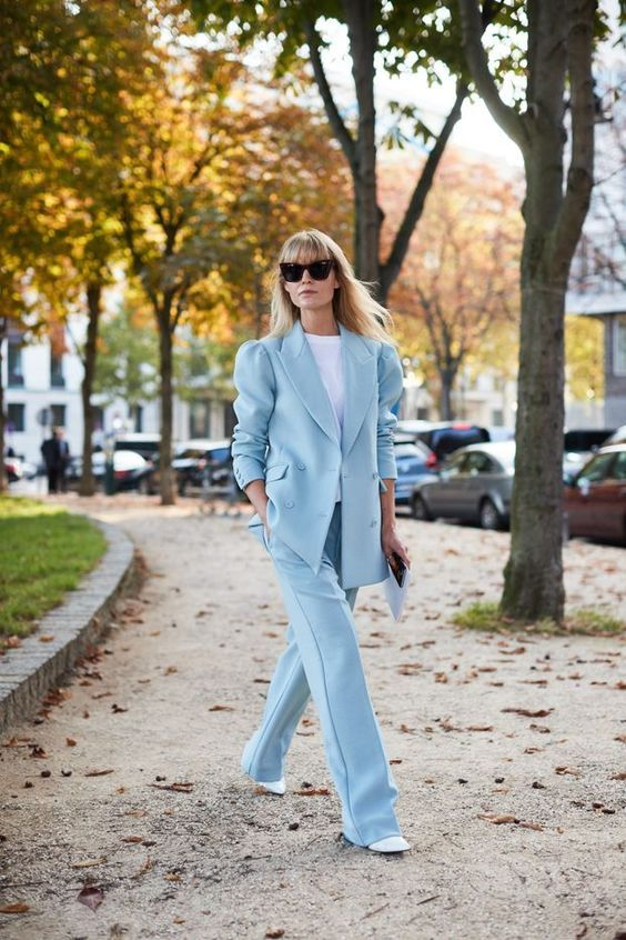 a light blue pantsuit with an oversized blazer, a white t shirt, white booties for a cool work look