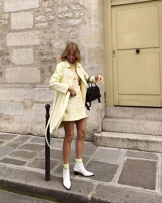 a light yellow look with a long sleeve top, a mini skirt, a short trench coat, yellow socks and white boots