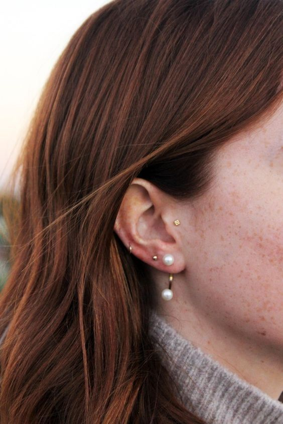 a minimalist gold square stud plus a little round one, a mini hoop and a statement pearl earring