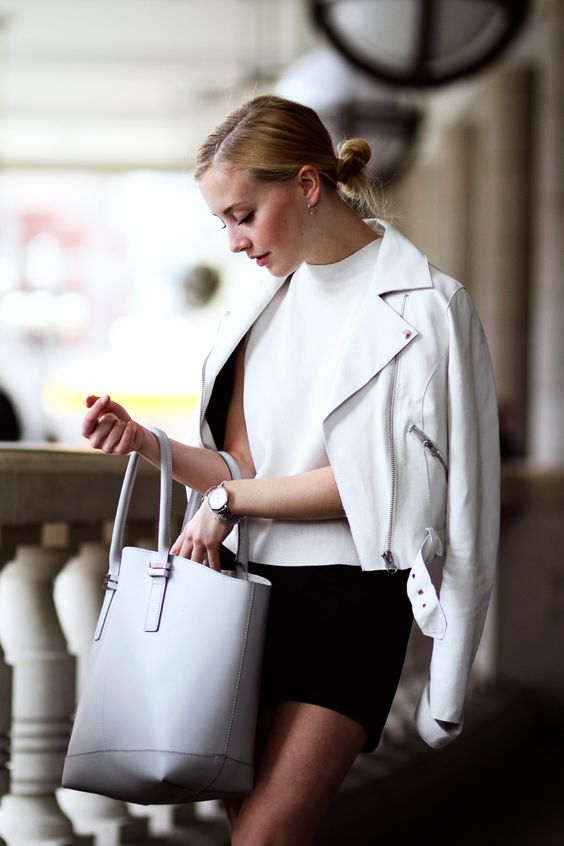 a minimalist outfit with a white top, a black mini skirt, a white leather jacket, a white tote