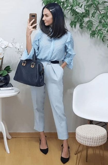 a monochromatic light blue outfit with a polka dot and ruffle blouse, trousers, black slingbacks and a navy bag
