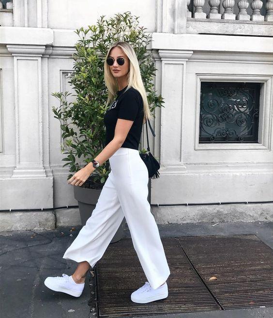 a monochromatic look with a black t-shirt, white wideleg pants, white platform sneakers, a black fringe bag
