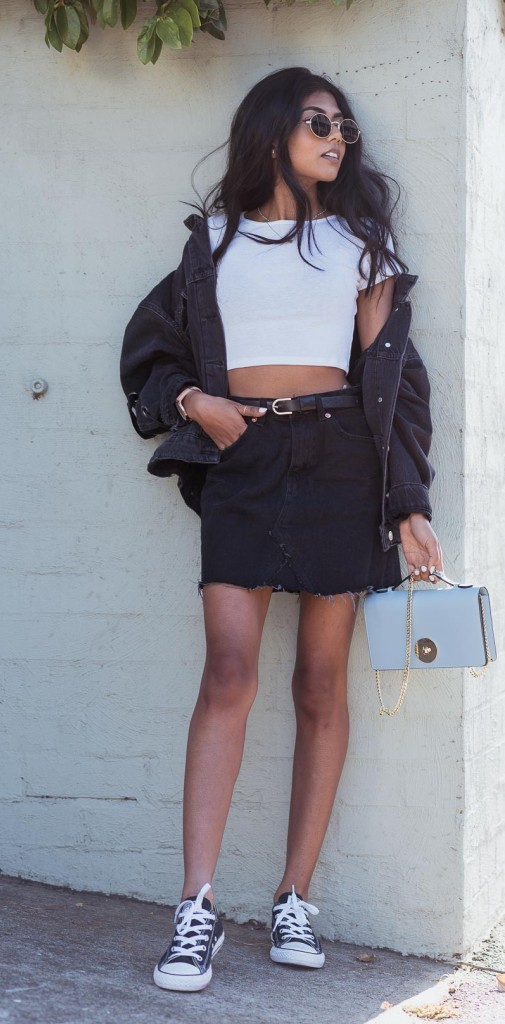 a monochromatic look with a white crop top, an oversized denim jacket, a mini skirt, black sneakers and a necklace