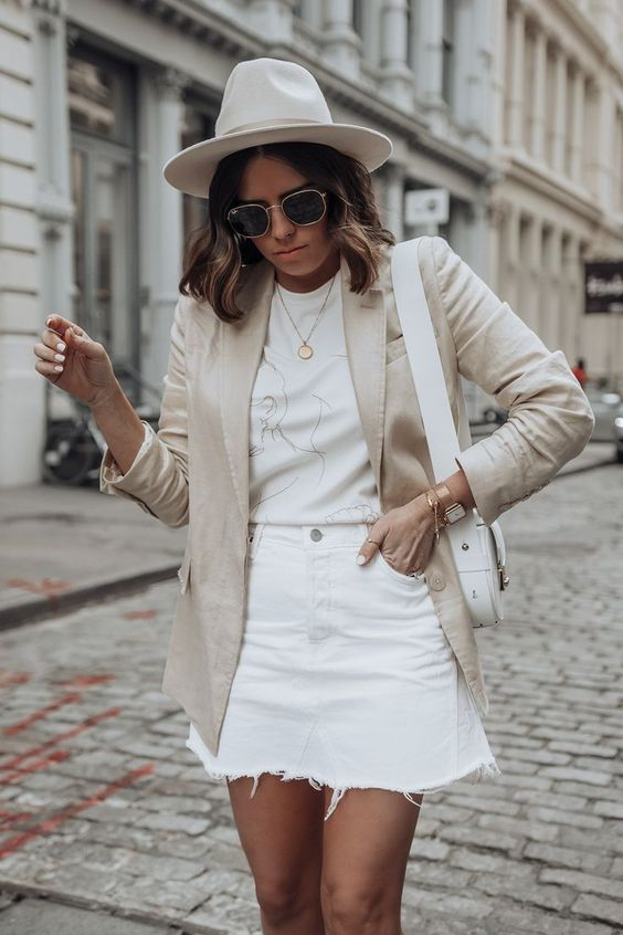 a neutral and chic look with a printed tee, white denim mini, a neutral linen blazer, a white hat and a small bag