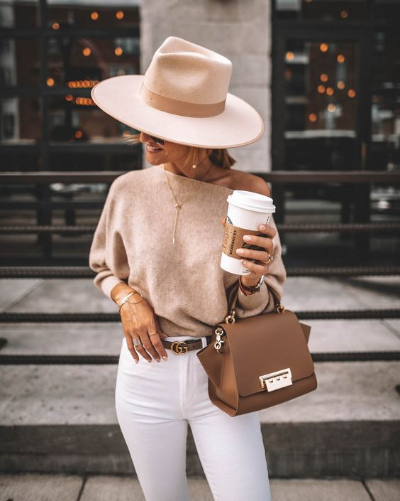a one shoulder tan top, white skinnies, a neutral hat, a brown bag and beautiful accessories