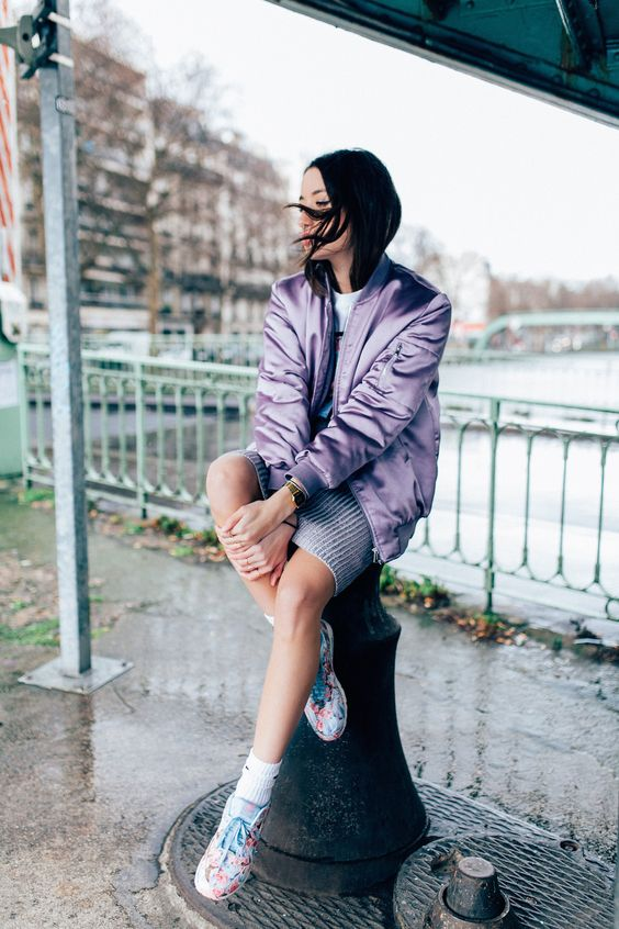 a pastel spring look with a pritned tee, a grey mini, a lilac bomber jacket and floral sneakers
