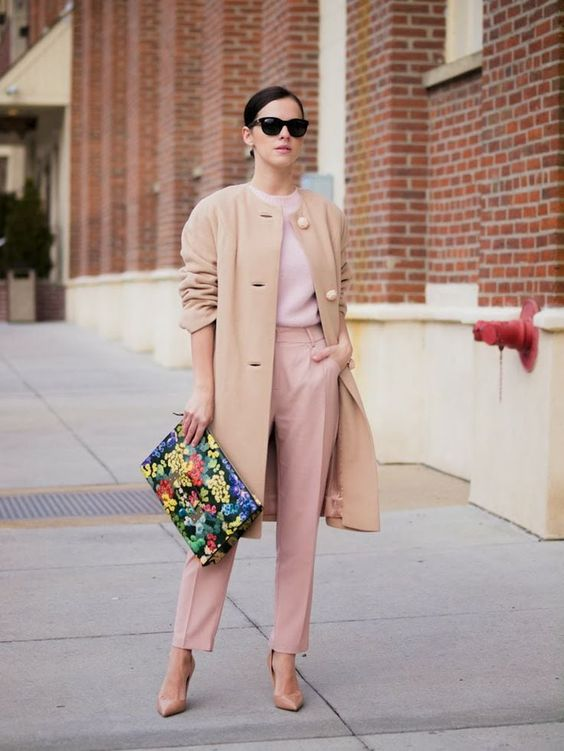 a pink long sleeve top, pink pants, blush shoes, a tan coat and a colorful large clutch for work