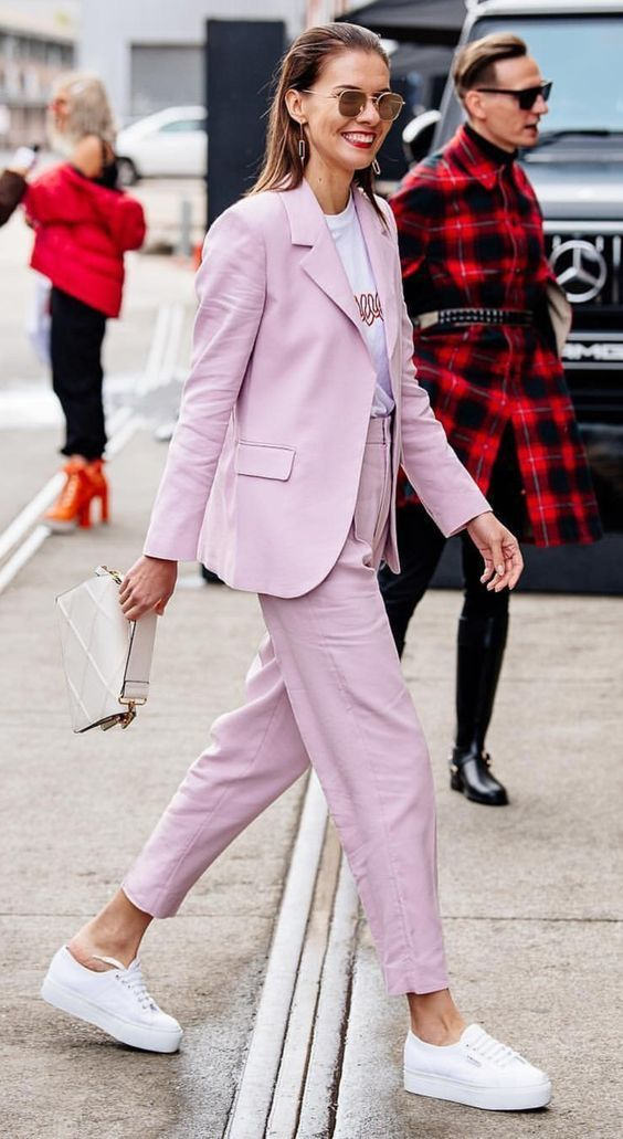 a pink pantsuit, a white printed t-shirt, white platform sneakers and a creamy bag for a whimsy work look