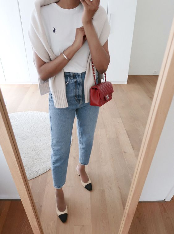 a preppy look with a white tee, blue mom jeans, two tone shoes, a white jumper and a red mini bag