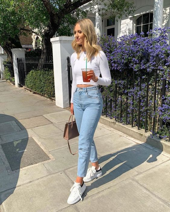 a pretty outfit with a white crop top, blue mom jeans, white sneakers and a tan bag