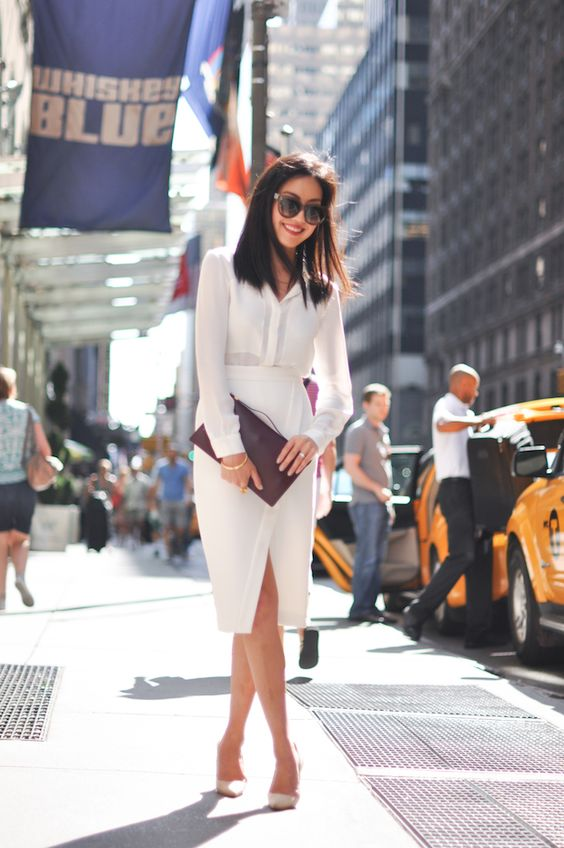 a refined work outfit with a white shirt, a white wrap pencil midi, white shoes and a purple clutch