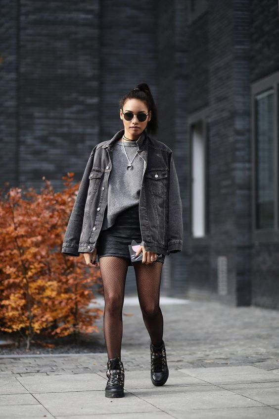 a rock look with a grey jumper, black leather mini, a black denim jacket, black boots and tights