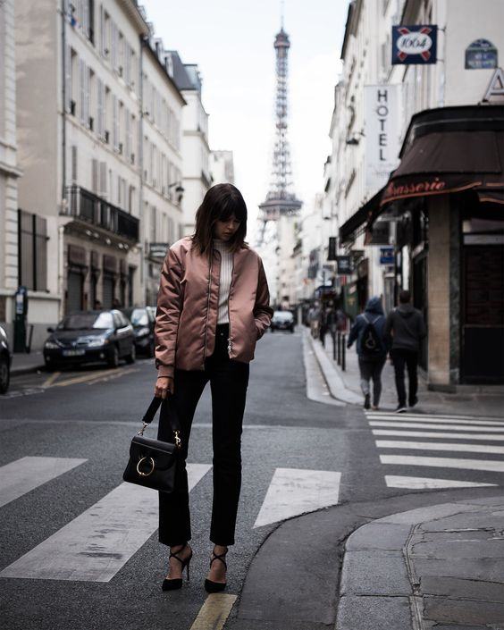 a romantic spring outfit with a white top, black straight leg jeans, black heels, a dusty rose bomber jacket and a black bag