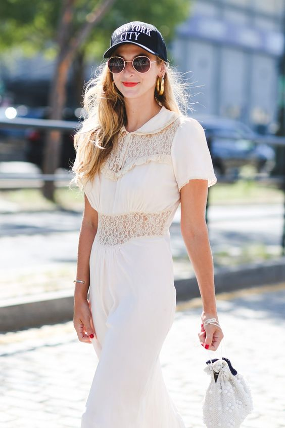 a romantic white dress with lace inserts, short sleeves, a grey beaded bag, a navy baseball hat and statement earrings
