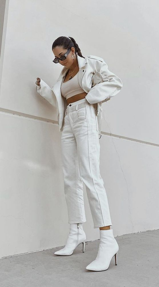 a sexy white look with a crop top, jeans, boots, an oversized white leather jacket and statement necklaces