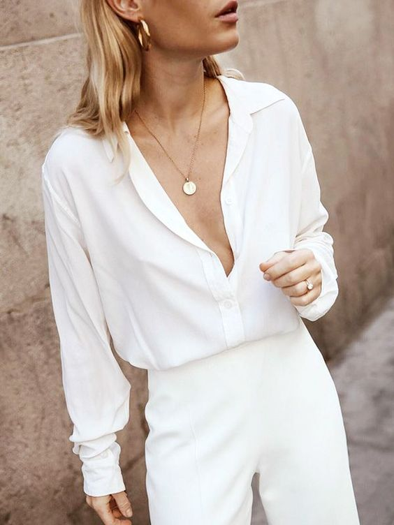 a simple and chic outfit with a white shirt and white trousers plus statement earrings and a necklace is cool