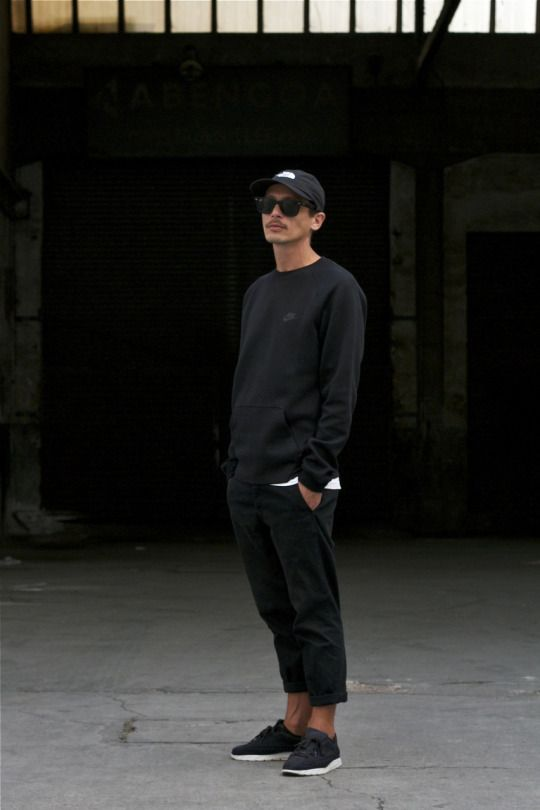 a simple total black look with sneakers, cropped pants, a sweatshirt over a white tee and a black baseball cap