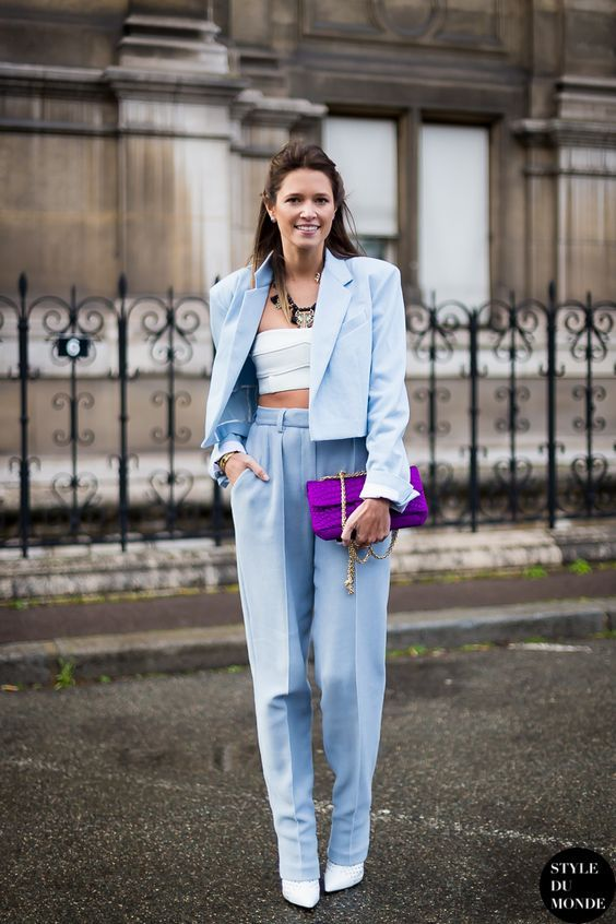 a sky blue pantsuit with a cropped blazer and accented shoulders, high rise trousers, white shoes and a purple bag