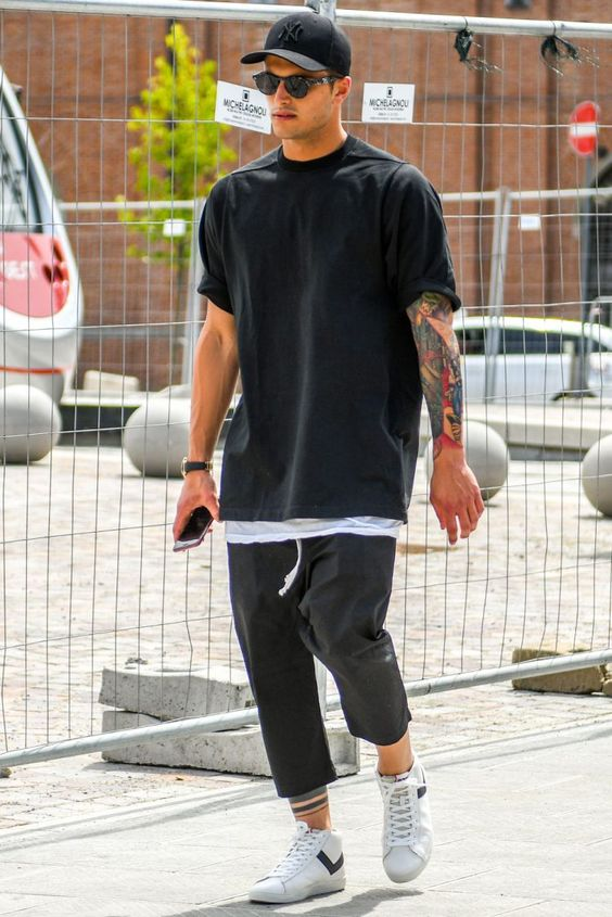 a sporty look with a black tee, black joggers, white sneakers and a black baseball hat