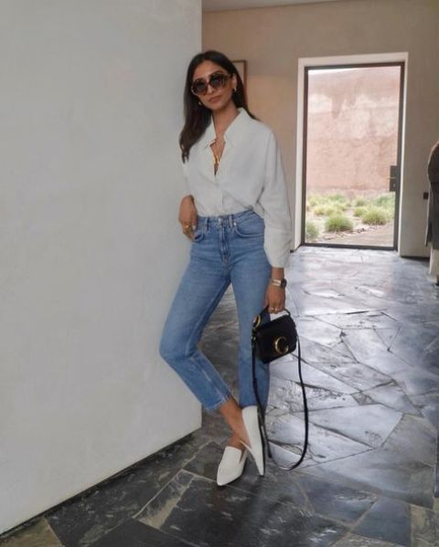 a spring work outfit with a white button up shirt, blue mom jeans, white loafers and a black mini bag