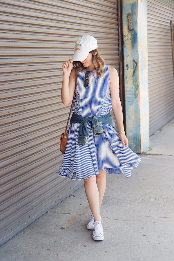 a striped blue knee dress, a blue denim jacket, a white baseball cap, white sneakers and a brown bag