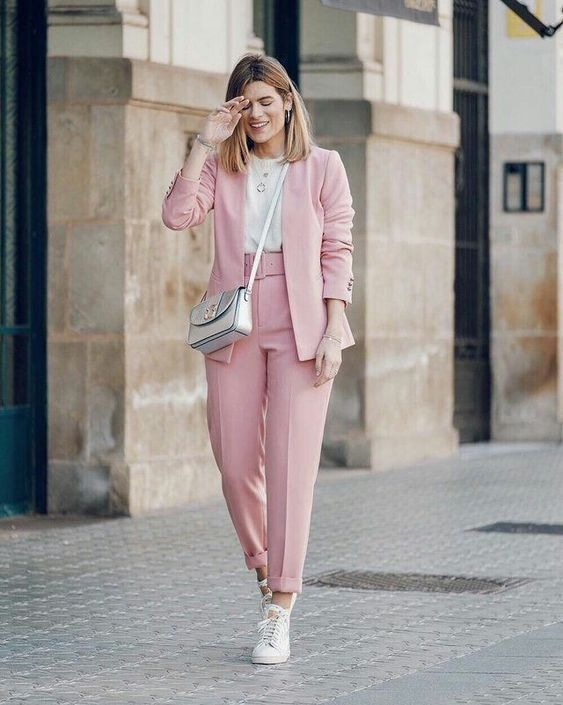 a stylish work look with a pink pantsuit, a white t shirt, white sneakers and a metallic crossbody bag